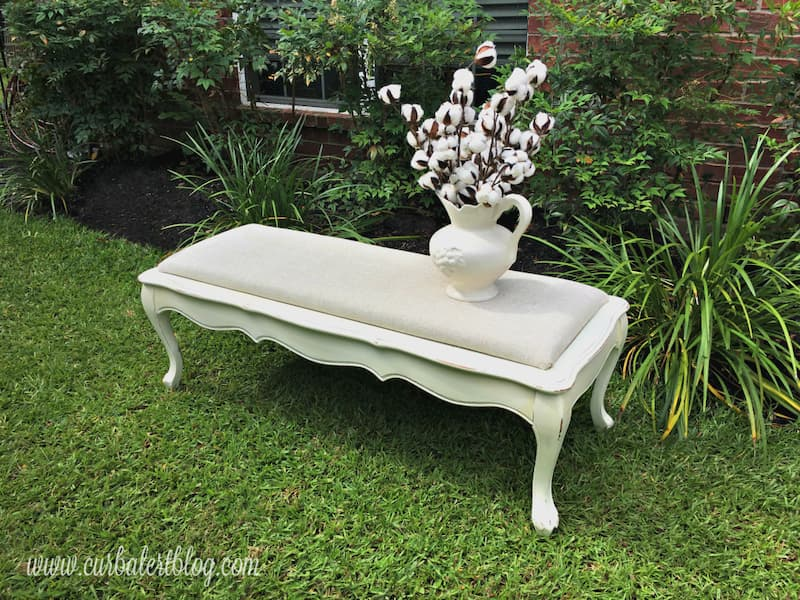 Coffee table ottoman finished in off white upholstery fabric