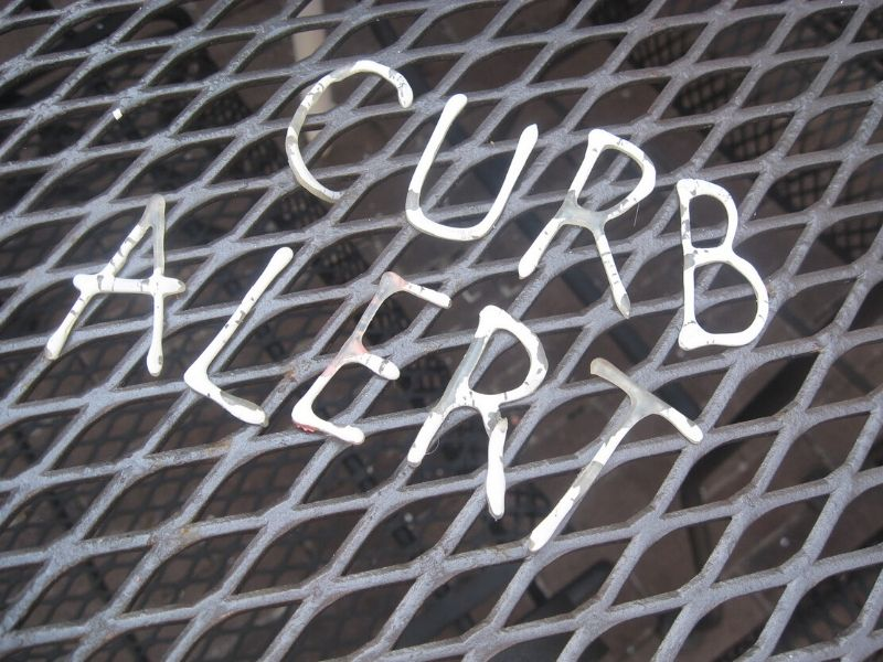 Curb alert words made out of puffy paint letters